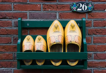 Storage rack with wooden shoes next to Dutch frontdoor Stock Photo