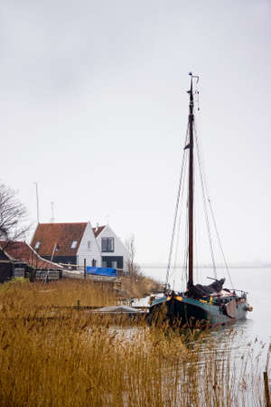Fishing village and boat at the lake on rainy day in winter photo