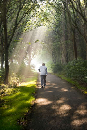 Middle aged man jogging on early summer morning in park