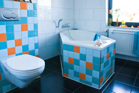 White bathroom, black floor, colorful decorated with tiles in light blue, azure blue and orange - horizontal   Stock Photo