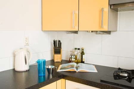 Cooking in colorful modern kitchen with cookbook and other photo
