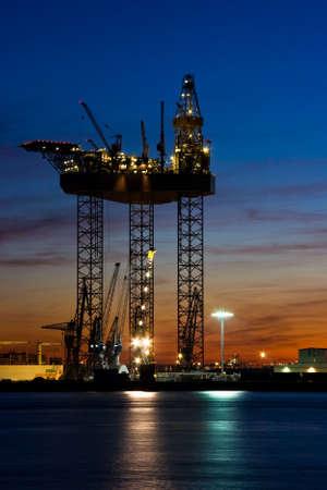 shiprepair: Big drilling platform in repair in the harbour at sunset