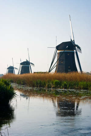Dutch watermills at the waterside with reflection after sunrise Stock Photo - 6816146