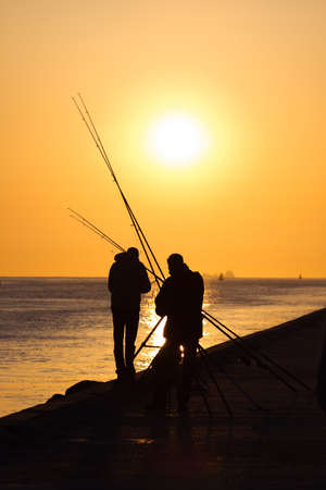 Fishermen on the pier - hazy and yellow sunset from volcanodust in the air