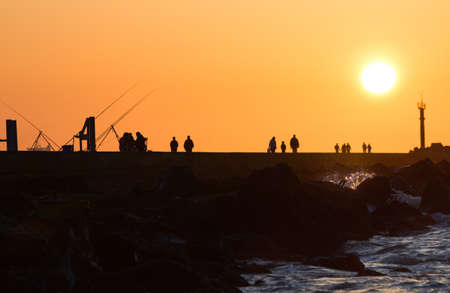 Pier with people fishing and walking - hazy and yellow sunset from volcanodust in the air photo