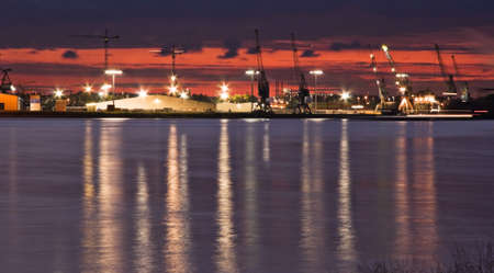 shiprepair: Container port with cranes at the riverside after sunset
