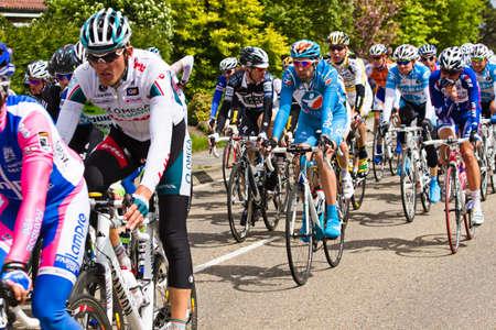 DELFGAUW, Nederland - 10 mei: Concurrenten en volgende teams in de Giro d�Italia doorgeven door een polderroad in de 3e fase van de wed strijd op 20 mei 2010, Delfgauw, Nederland.  Redactioneel