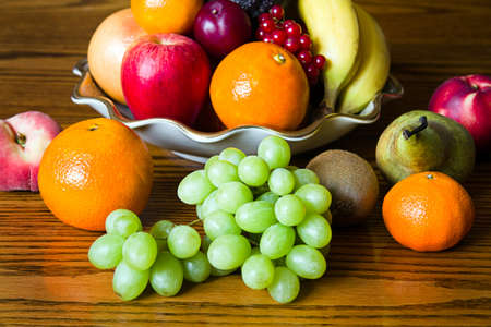 Selection of colorful, fresh, natural looking fruit in an old bowl placed on wood. Stock Photo