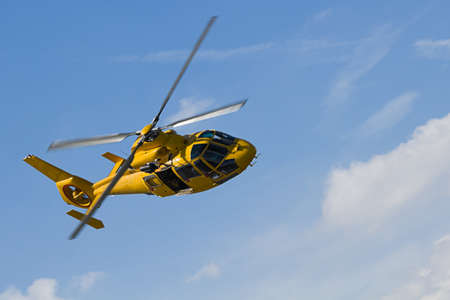 Yellow helicopter flying in blue sky with clouds Stock Photo