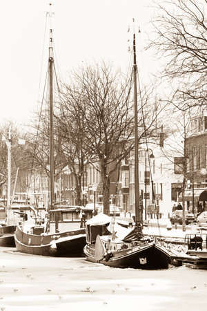 fishingboats: Fishingboats in the harbor with winter  ice and snow - old fashioned sepia image
