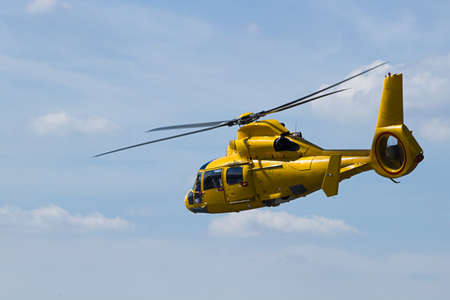 Yellow Helicopter flying in cloudy sky