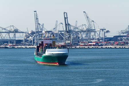 containership: Containership on the river with industry and cranes in background Stock Photo