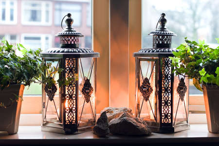 winterday: Lanterns with burning candles in window on rainy winterday - homelike inside, cold outside Stock Photo