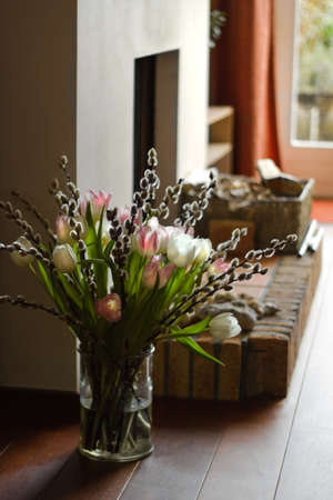 hearth: Part of interior with fireplace and bouquet of springflowers - vertical Stock Photo