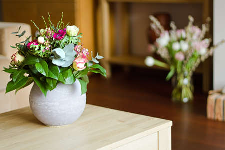 Part of modern interior with two bouquets of flowers -  shallow dof