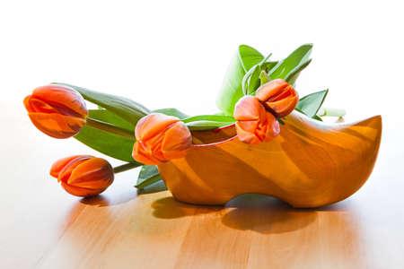 Saluut vanuit Nederland - Nederlandse klompen en oranje tulpen met witte achtergrond op houten tafel Stockfoto
