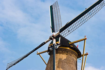 Blades of historic Dutch windmill still in use to grind corn with blue sky background photo