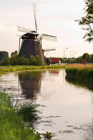 Dutch windmills with reflection after sunrise in spring - vertical Stock Photo - 9552342