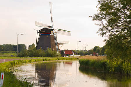 Dutch windmills with reflection after sunrise in spring - horizontal Stock Photo - 9552343