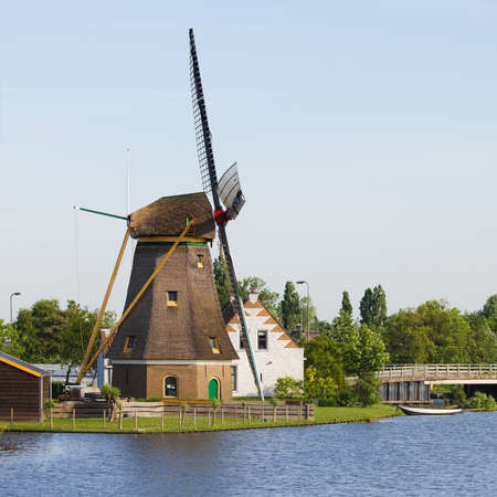 Dutch windmill, house and bridge at the waterside - square Stock Photo - 9552339