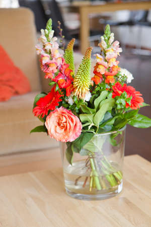 Modern interior with bouguet of flowers in glass vase on table photo