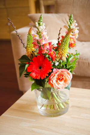 Bouguet of flowers in glass vase on table in modern interior with shallow dof Stock Photo - 9552349