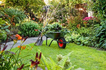 jardinero: Noche después del trabajo en el jardín de verano con carretilla, pala y rastrillo - horizontal