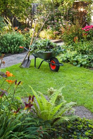 Evening after work in summer garden with wheelbarrow, shovel and rake - vertical photo