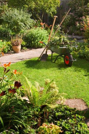 carretilla: Trabajo en el jard�n de verano en la ma�ana con la carretilla, pala y rastrillo - vertical
