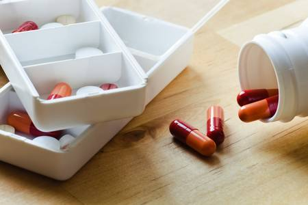 Pills, capsules and tablets sorted in medicine box for use as daily medication photo