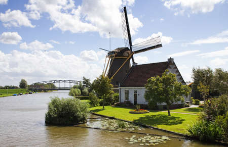 dutch landmark: Typical Dutch landscape -  windmill, house and bridge at the waterside Stock Photo