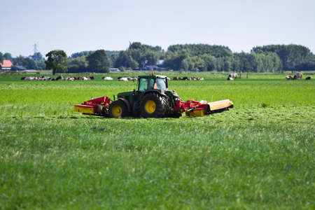Farmer on the field with tractor and lawn-mower on early morning in summer Stock Photo