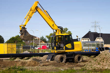 equalize: Excavator at work digging up ground for new to build houses - horizontal