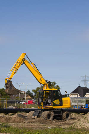 equalize: Excavator at work digging up ground for new to build houses - vertical