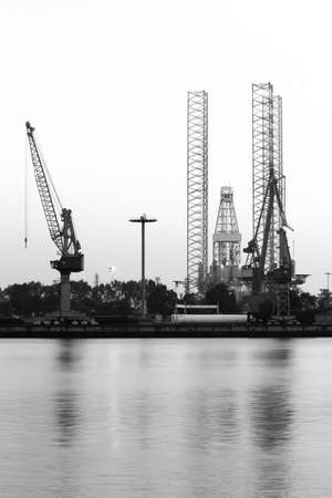 shiprepair: Construction- and ship-repair industry, cranes and drilling rig - vertical black and white image Stock Photo