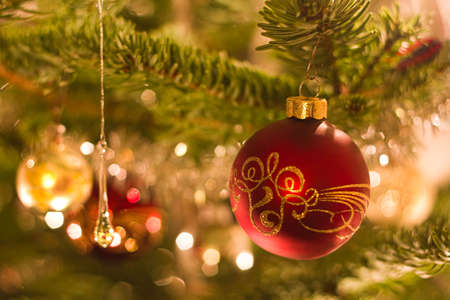 Decorated ball in christmas tree with other decoration and lights - shallow dof horizontal