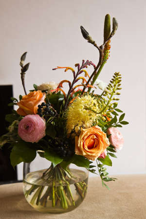 roses in vase: Bouquet of flowers in glass vase with modern fireplace in background