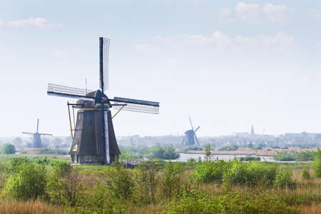 Country landscape with windmills at Kinderdijk, the Netherlands on hazy day in spring photo
