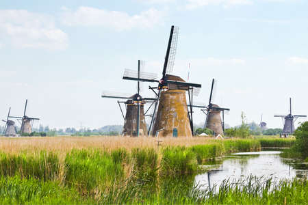 Dutch countrylandscape in Kinderdijk, the Netherlands with eight from the nineteen windmills on hazy day  photo