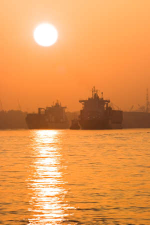 containership: Containerships and tug on the river with a misty red sunrise - vertical Stock Photo