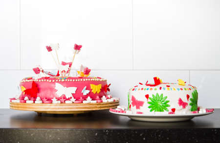marzipan: Colorful decorated white and pink Marzipan cakes for a birthday party on kitchen dresser