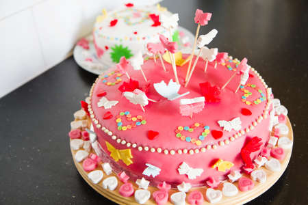 marzipan: Colorful decorated white and pink Marzipan cakes for a birthday party on kitchen dresser  Stock Photo