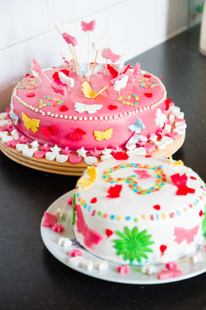 marzipan: Delicious colorful decorated white and pink Marzipan cakes for a birthday party on kitchen dresser