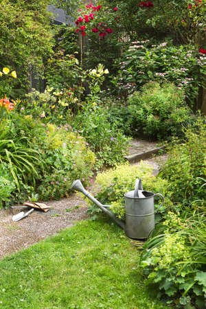summergarden: Watering-can and garden tools for cleaning blooming cottage-style garden on summer morning - vertical Stock Photo