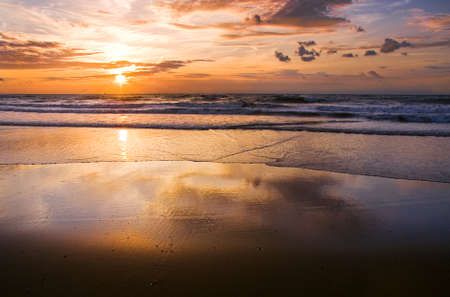sunrise beach: Colorful cloudy sunset at the beach with reflection - horizontal Stock Photo