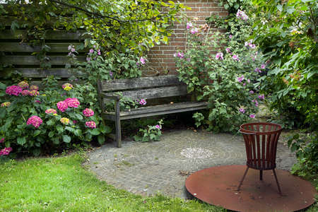 Country-style garden with bench, fireplace and lots of flowers in summer