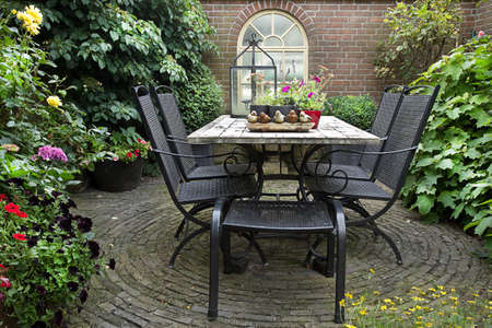 Iron forged table and chairs in garden with flowers, table decoration and potplants in summer