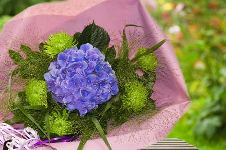 Blue and green bouquet of flowers wrapped in paper with summer garden background photo