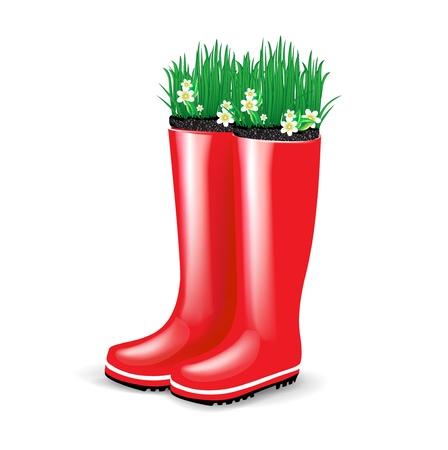 bottes en caoutchouc rouge avec de l'herbe et des fleurs épanouies isolé