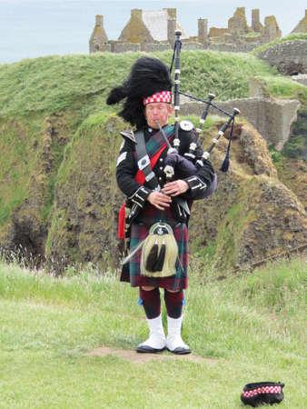 gaita: Gaitero solitario frente al Castillo de Dunnottar, cerca de Stonehaven, Escocia Editorial